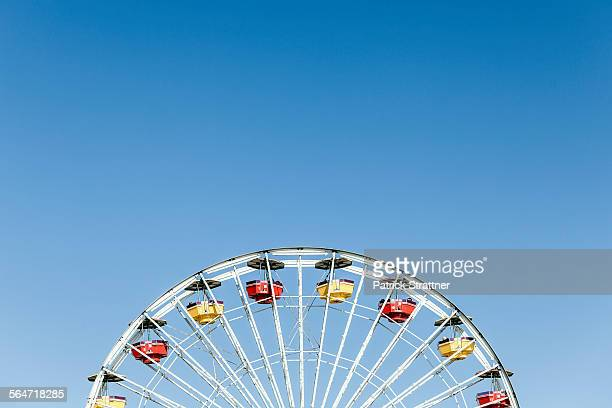 low angle view of ferris wheel against clear blue sky - santa monica stock-fotos und bilder