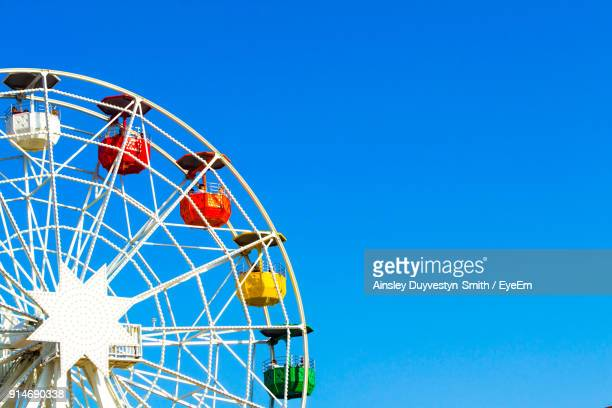low angle view of ferris wheel against clear blue sky - ferris wheel stock pictures, royalty-free photos & images