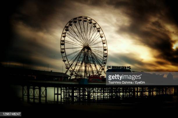 low angle view of ferris wheel against cloudy sky - blackpool stock pictures, royalty-free photos & images