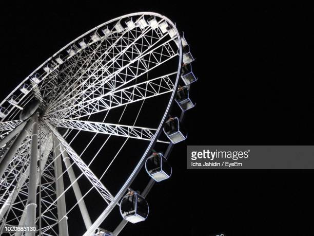 low angle view of ferris wheel against sky at night - 観覧車 ストックフォトと画像
