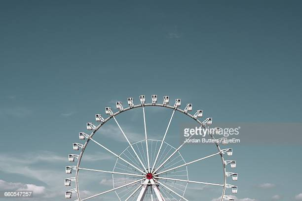 low angle view of ferris wheel against sky on sunny day - 観覧車 ストックフォトと画像