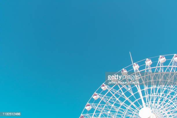 low angle view of ferris wheel against sky - jeffrey roque stock photos and pictures