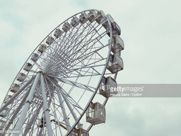 low angle view of ferris wheel against sky - 観覧車 ストックフォトと画像