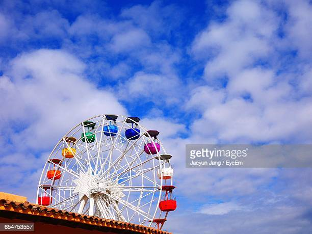 low angle view of ferris wheel against the clouds - tibidabo stock pictures, royalty-free photos & images