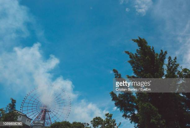 Low Angle View Of Ferris Wheel And Trees Against Cloudy Sky
