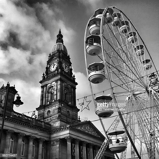Low Angle View Of Ferris Wheel By Bolton Town Hall Against Cloudy Sky