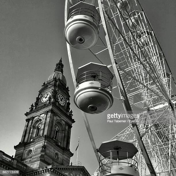 Low Angle View Of Ferris Wheel By Bolton Town Hall Against Sky