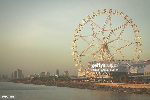 Low Angle View Of Ferris Wheel By Manila Bay Against Sky