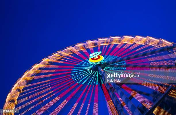 Low angle view of ferris wheel lit up at night