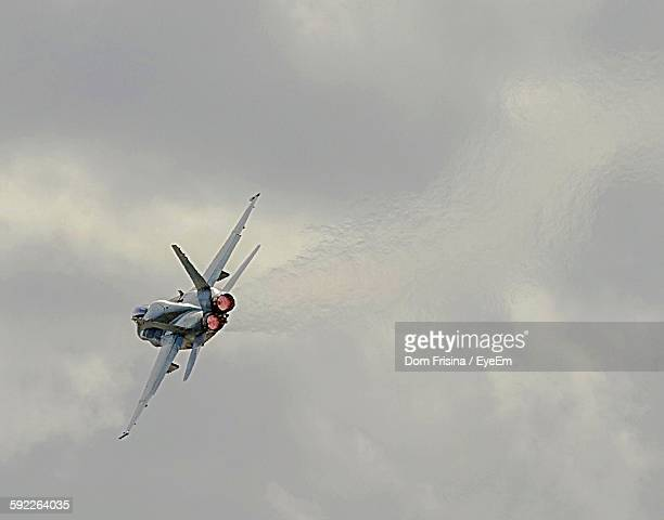 low angle view of fighter plane against sky - avion de chasse photos et images de collection