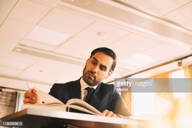 low angle view of financial advisor reading book at table in office - legal system stock pictures, royalty-free photos & images