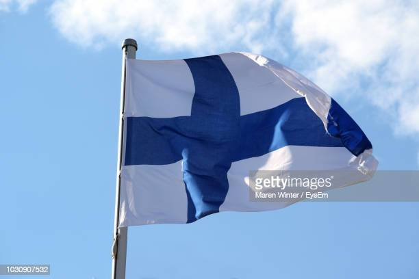 low angle view of finnish flag against blue sky - finnish flag stock photos and pictures