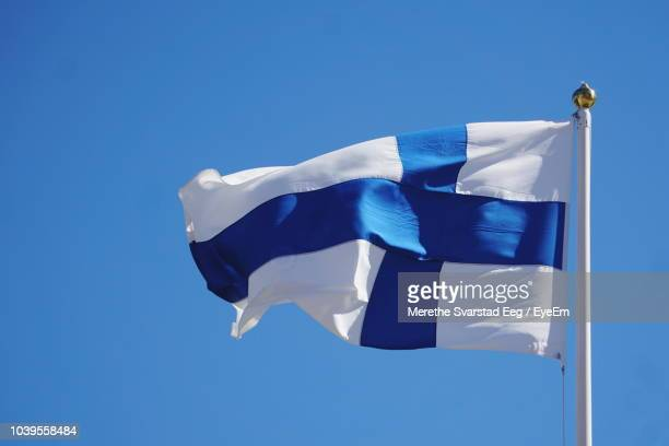 low angle view of finnish flag waving against clear blue sky - finnish flag stock photos and pictures