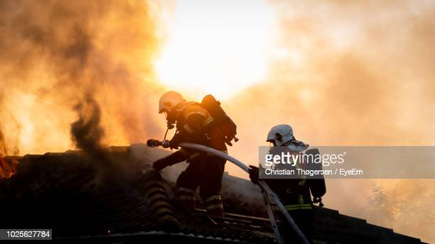 low angle view of firefighters with fire hose against smoke - rescue services occupation stock photos and pictures