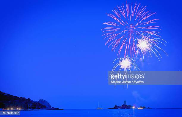 Low Angle View Of Firework Display Against Blue Sky