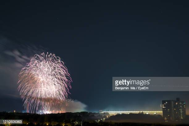 low angle view of firework display against sky at night in berlin germany - olympiastadion berlin stock pictures, royalty-free photos & images