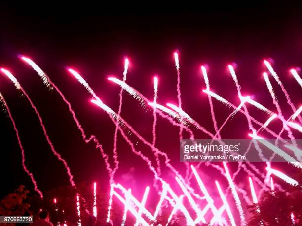 low angle view of firework display against sky at night - daniel funke stock-fotos und bilder