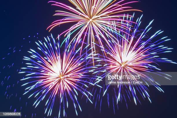 low angle view of firework display at night - fireworks stock pictures, royalty-free photos & images