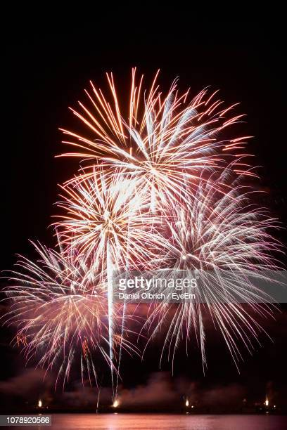 low angle view of firework display at night - daniel funke stock-fotos und bilder
