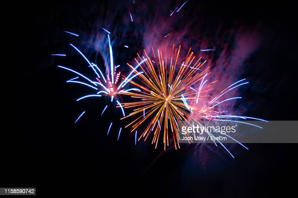 low angle view of firework display at night - josh utley stock pictures, royalty-free photos & images
