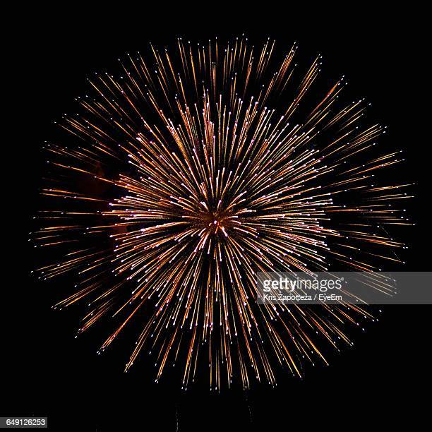 low angle view of firework display at night - form stock-fotos und bilder