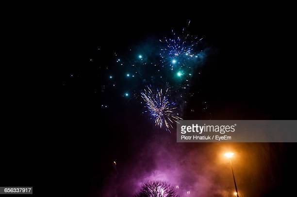 low angle view of firework display at night - piotr hnatiuk imagens e fotografias de stock