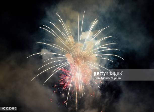 low angle view of firework display at night - evan agostini stock pictures, royalty-free photos & images