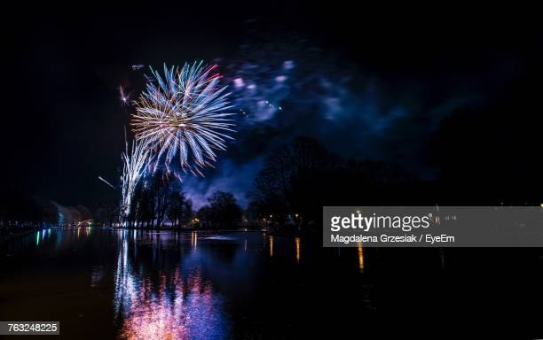 Low Angle View Of Firework Display By River At Night