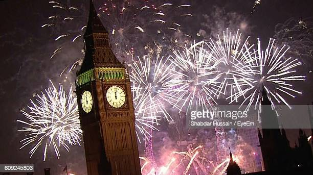 Low Angle View Of Firework Display Over Big Ben And Millennium Wheel At Night