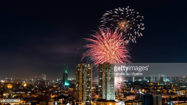 low angle view of firework display over buildings against sky - philippinen stock-fotos und bilder