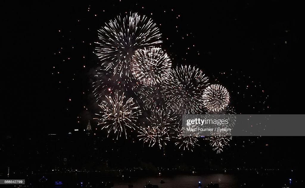 Low Angle View Of Firework Display Over City At Night : Stock Photo