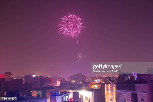 low angle view of firework display over cityscape against sky at night - diwali celebration stock photos and pictures