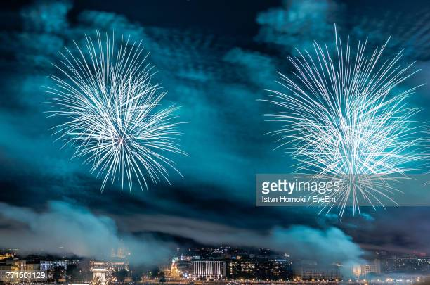 Low Angle View Of Firework Display Over Illuminated City At Night
