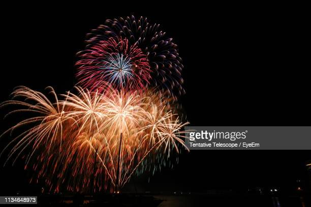 Low Angle View Of Firework Display Over River Against Sky At Night