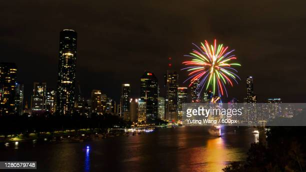 low angle view of firework display over river against sky at night,brisbane qld,australia - wang he stock pictures, royalty-free photos & images