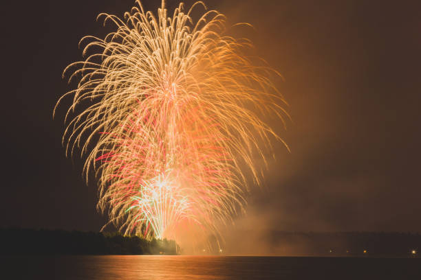 Low angle view of firework display over river against sky at night,Belarus