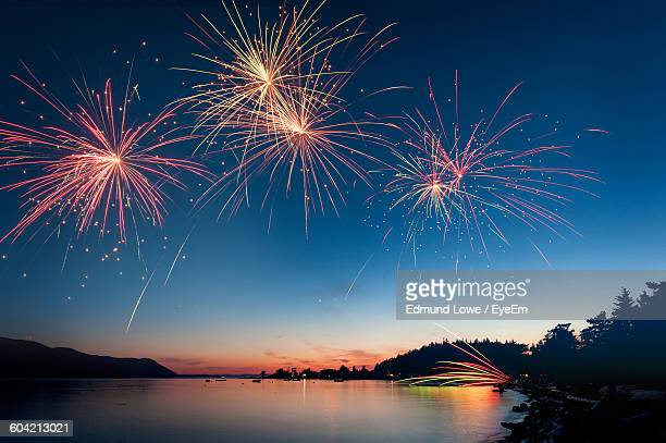 low angle view of firework display over river during sunset - fireworks stock pictures, royalty-free photos & images