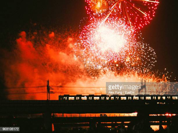 Low Angle View Of Firework Display Over Train Against Sky At Night