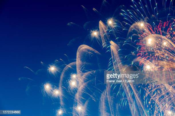 low angle view of fireworks against sky at night - firework display stock pictures, royalty-free photos & images