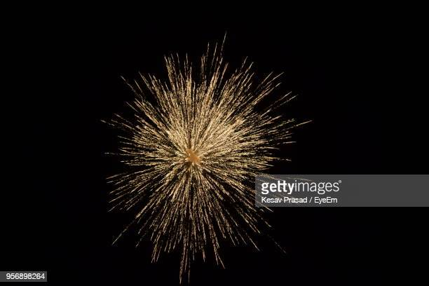 low angle view of fireworks against sky at night - firework display stock photos and pictures