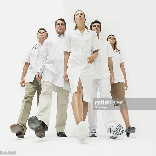 low angle view of five doctors walking together - low angle view stock pictures, royalty-free photos & images