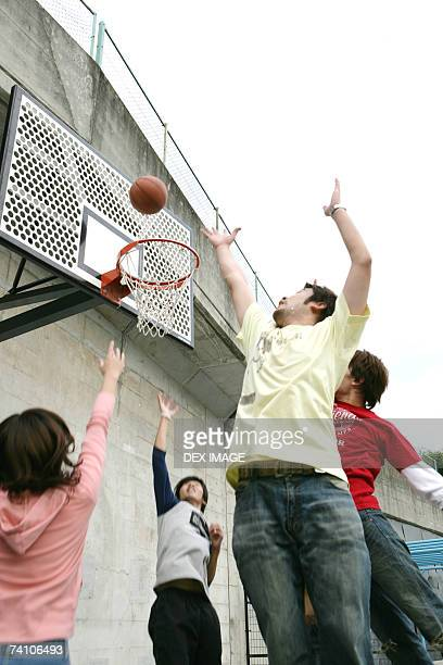 Low angle view of five people shooting a basket ball into a hoop