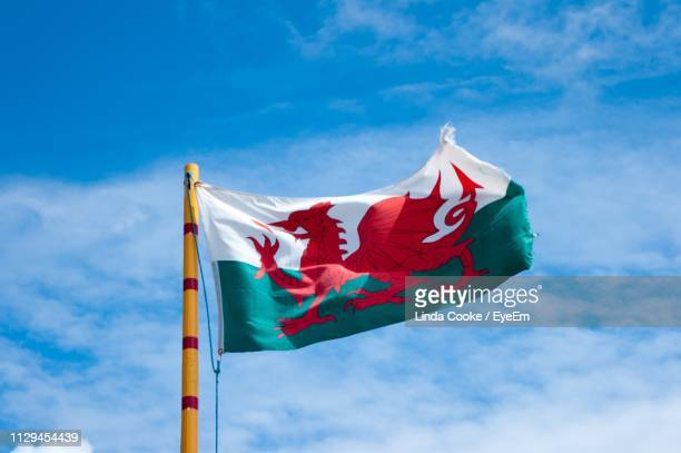 low angle view of flag against blue sky - welsh flag stock pictures, royalty-free photos & images