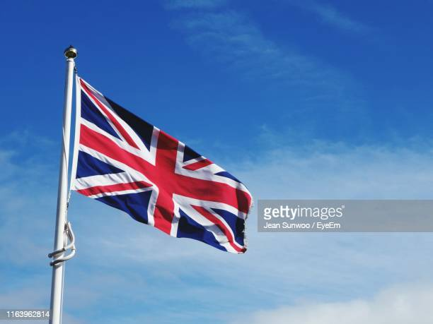 low angle view of flag against blue sky - union jack stock pictures, royalty-free photos & images