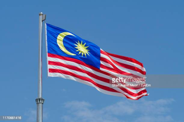 low angle view of flag against blue sky - shaifulzamri eyeem stock pictures, royalty-free photos & images