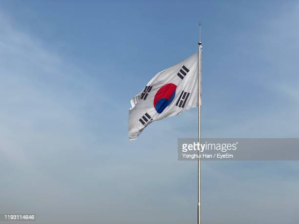 low angle view of flag against blue sky - south korea stock pictures, royalty-free photos & images