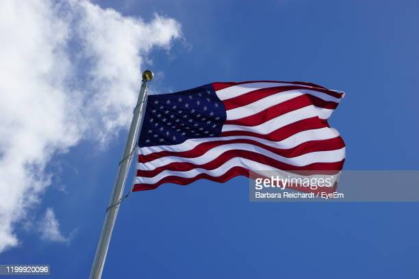 low angle view of flag against blue sky - hawaii flag stock pictures, royalty-free photos & images