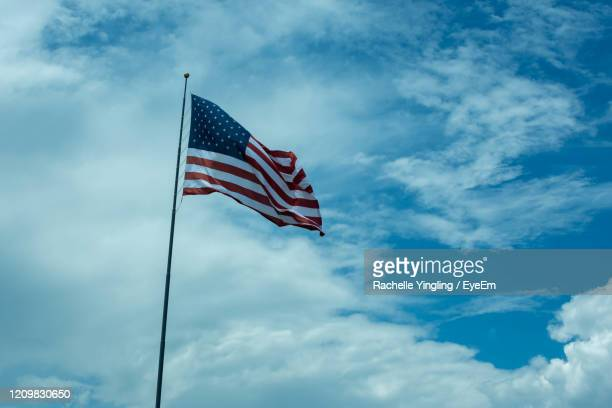 low angle view of flag against blue sky - flag day stock pictures, royalty-free photos & images