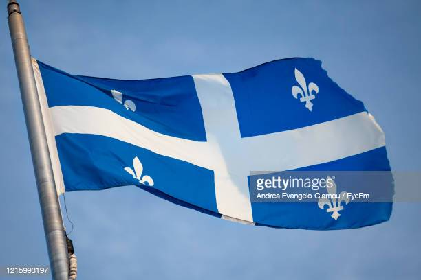 low angle view of flag against blue sky - quebec stock pictures, royalty-free photos & images