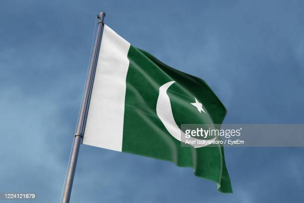 low angle view of flag against blue sky - pole stock pictures, royalty-free photos & images
